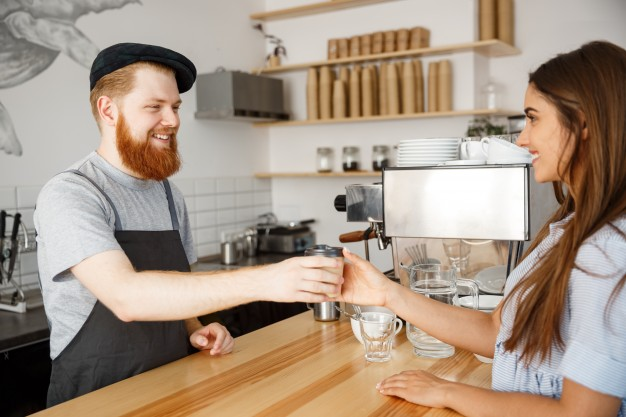 coffee business concept young beared handsome barista talking and giving take away hot coffee for beautiful caucasian customer in modern coffee shop 1258 613
